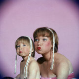 Actress Shirley MacLaine and Daughter Sachi Parker Pouting with String of Pearls on Their Heads Lámina fotográfica prémium por Allan Grant