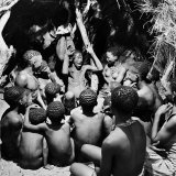 Chief Acts Out a Story to Bushman Children, Southern Kalahari Desert in Central Southern Africa Reproduction photographique par Nat Farbman