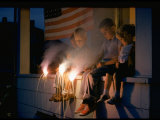 Boys Sitting on Porch Holding Sparklers, with US Flag in Back, During Independence Day Celebration Reproduction photographique par Nat Farbman