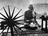 Indian Leader Mohandas Gandhi Reading as He Sits Cross Legged on Floor Reproduction photographique Premium par Margaret Bourke-White