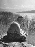 Swiss Psychiatrist Dr. Carl Jung Sitting on Stone Wall Overlooking Lake Zurich Impressão fotográfica premium por Dmitri Kessel