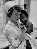 Nurse Holding African American Girl in Her Arms, Examining Her Finger Fotografisk trykk av John Dominis