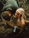 Shell Shocked American Marine Getting Wounds Bandaged in Muddy Jungle During OP Prairie Reproduction photographique par Larry Burrows