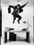 Architect and Designer Frank Gehry Jumping on a Desk in His Line of Cardboard Furniture Premium Photographic Print by Ralph Morse