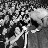Comedian Milton Berle Trying to Kiss Fans Who Are Asking for Autographs Premium Photographic Print by George Silk