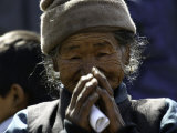 Old Woman with Hands to Face, Nepal Fotografie-Druck von David D'angelo