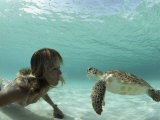 A Young Woman Swimming Face-To-Face with a Green Sea Turtle Impressão fotográfica por Bill Curtsinger