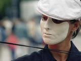 A Street Performer Wears a Mask Concealing Her Expression Fotografisk tryk af Jim Webb