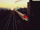 A Trans-Canada Railway Train Rushes Down the Tracks at Dusk Fotografisk tryk af Paul Chesley