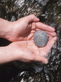 Person Holding Rock with the Word Blessings in Rushing Water Fotografie-Druck