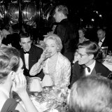 Marlene Dietrich with Yves St. Laurant in Paris at Dinner Table in Restaurant, November 1959 Photographic Print