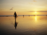 A Surfer with a Surfboard in Hand Walks Toward the Ocean at Sunset Fotografisk trykk