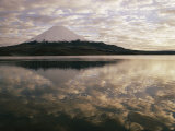 View of Snowcapped Payachata Volcano and a Cloudy Twilight Sky Mirrored in the Lake Impressão fotográfica por George F. Mobley