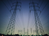Setting Sun Silhouettes Tall, High-Tension-Wire Towers Photographic Print by Emory Kristof