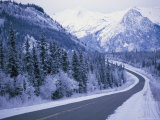 Winter View of the Highway Surrounded by Snow-Covered Mountains Stampa fotografica di Klaus Nigge