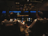 Pilots Sitting in the Cockpit at Night Fotografisk tryk af Paul Chesley