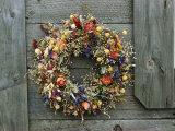 A Delicate Dried Flower Wreath Adorns a Wooden Wall Near a Window Impressão fotográfica por Bill Curtsinger