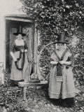 Two Welshwomen in Traditional Dress Stand Outside Their Cottage with a Spinning Wheel Fotografisk trykk