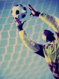 Low Angle View of a Goalie Catching a Ball Lámina fotográfica