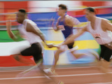 Side Profile of Runners Exchanging Baton at a Relay Race Photographic Print