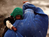 An Afghan Woman Holding Her Child Throws Back Her Burqa to See Her Way Along a Muddy Alley Stampa fotografica