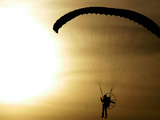 An Engine-Powered Paraglider Soars Through the Air Near Schlesen Fotografisk trykk