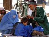 A Mother Watches as Her Child Gets a Haircut in the Center of Kabul, Afghanistan on Oct. 9, 2003. Stampa fotografica