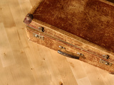An Old Battered Brown Suitcase on a Wooden Floor Photographic Print