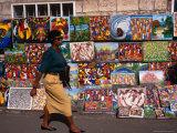 Woman Walking Past Art Stall, St. John's, Antigua & Barbuda Photographic Print by Wayne Walton
