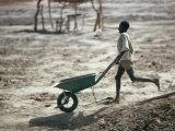 Boy Running with Wheelbarrow, Burkina Faso Lámina fotográfica por Eric Wheater