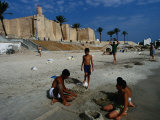 Children Playing on Beach in Front of Restored Fort Ribat, Monastir, Tunisia Fotografie-Druck von Damien Simonis