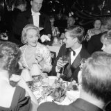 Marlene Dietrich with Yves St. Laurant in Paris Sitting in a Restaurant, November 1959 Photographic Print
