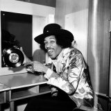 American Musician Jimi Hendrix in Dressing Room Holding a Copy of Single, Earing a Black Hat Fotografie-Druck
