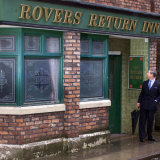 """Prince Charles Shelters from the Rain on the Set of """"The Soap Coronation Street"""" Fotografisk tryk"""