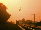 Aerial Crop Duster and Train at Sunrise Photographic Print by Rex Stucky