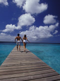 Couple Running on Dock, Curacao, Caribbean Fotografisk trykk av Greg Johnston