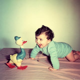 Baby Crawling Next to a Toy Duck Photographic Print by A. Villani