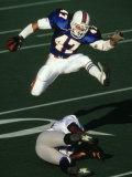 Football Running Back Flys over the Defense Fotografie-Druck