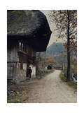 Man Stands Outside a Farmhouse Along a Pathway in the Black Forest Photographic Print by Hans Hildenbrand