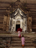 Young Burmese Girls Emerge from a Temple Carved in Rock Fotografisk tryk af Paul Chesley