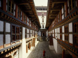 Monk Walks Through the Fortress-Style Architecture of a Dzong Fotografisk tryk af Paul Chesley