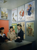 Flight Attendants Stand and Talk Beneath Airline Advertising Posters Photographic Print by B. Anthony Stewart