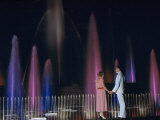 Couple Holding Hands Watches Water Fountains Illuminated at Night Photographic Print by B. Anthony Stewart