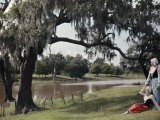 Two Women Rest Beneath a Tree, Beside the Bayou Teche Waters Reproduction photographique par Edwin L. Wisherd