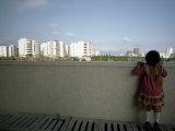 Little Girl Looks over a Wall Toward High Rises Near Hong Kong Fotografisk trykk av Lynn Johnson