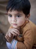 Boy Waits to Receive a Ration of Donated Rice at Food Distribution Center in Islamabad, Pakistan Impressão fotográfica