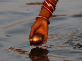Woman Praying on the Banks of the River Ganges Fills Water into a Copper Vessel for a Ritual Impressão fotográfica