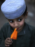 Boy Eats an Ice Lolly in a Neighborhood on the Outskirts of Islamabad, Pakistan Reproduction photographique