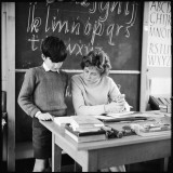 A Boy Pupil Reading with His Teacher, at Her Desk in Front of the Blackboard Photographic Print by Henry Grant