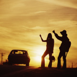 Silhouetted Couple Hitchhiking on Roadside Photographic Print by Dennis Hallinan